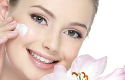 Smiling woman with lily applying cream